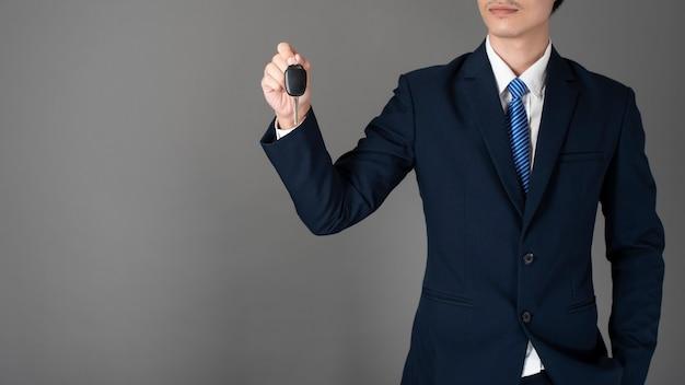 L'uomo di affari sta tenendo la chiave dell'automobile, fondo grigio in studio Foto Premium