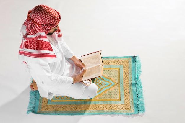 L'uomo di alta vista che si siede sul tappeto di preghiera e legge Foto Gratuite
