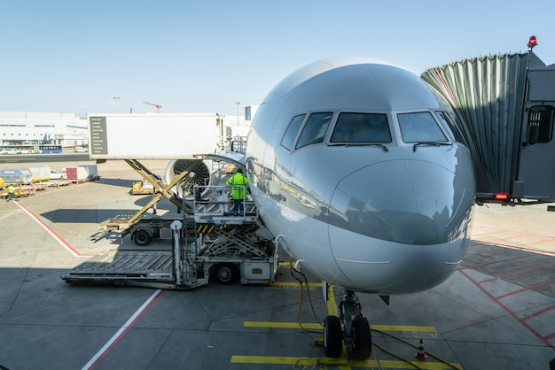 L'uomo di carico sulla piattaforma di carico carica il trasporto aereo verso gli aerei cargo. Foto Premium