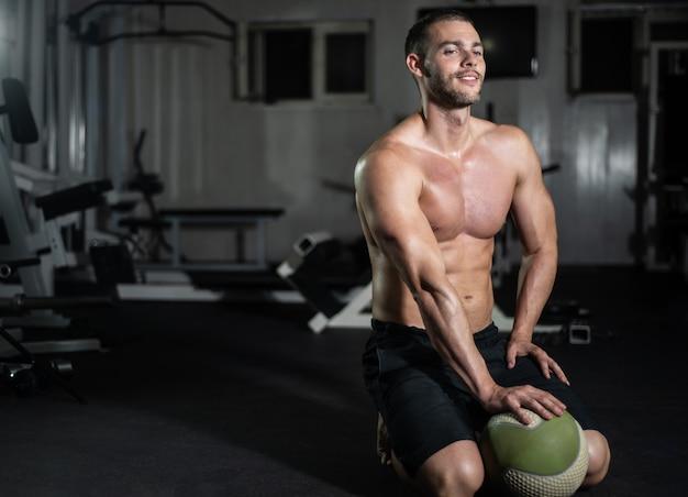 L'uomo di forma fisica posa con una palla in palestra Foto Premium