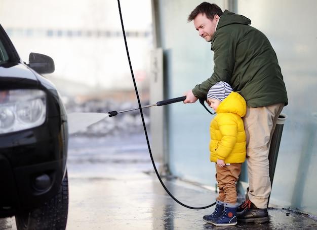 L'uomo di mezza età e il suo piccolo figlio lavare un'auto su un autolavaggio. tempo per la famiglia Foto Premium