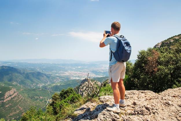 L'uomo di viaggio con la condizione dello zaino prende una foto dallo spazio di sunny day dello smartphone mountians Foto Premium
