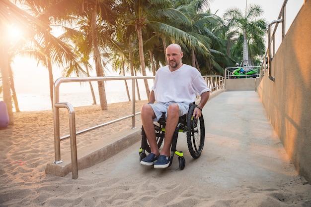 L'uomo disabile in sedia a rotelle si muove su una rampa verso la spiaggia. Foto Premium