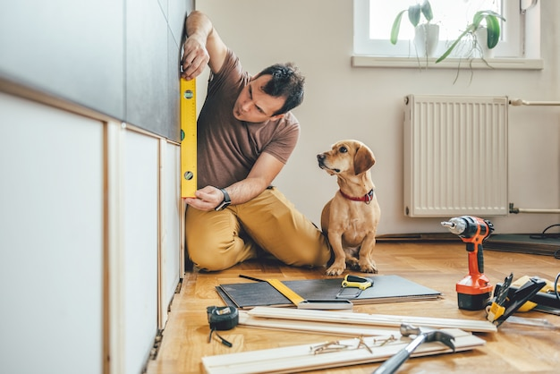 L'uomo e il suo cane facendo lavori di ristrutturazione a casa Foto Premium