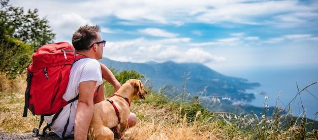 L'uomo e il suo cane seduto sulla montagna e guardando il mare Foto Premium