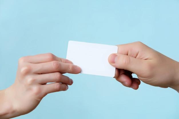 L'uomo e la donna che danno le mani di plastica della carta si chiudono su isolato, copiano lo spazio Foto Premium