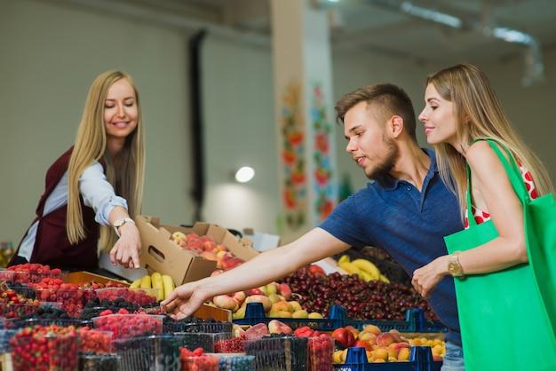 L'uomo e la donna comprano le bacche al mercato Foto Premium