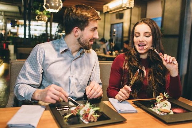 L'uomo e la donna mangiano al tavolo del ristorante e parlano tra loro. si stanno godendo l'un l'altro. Foto Premium