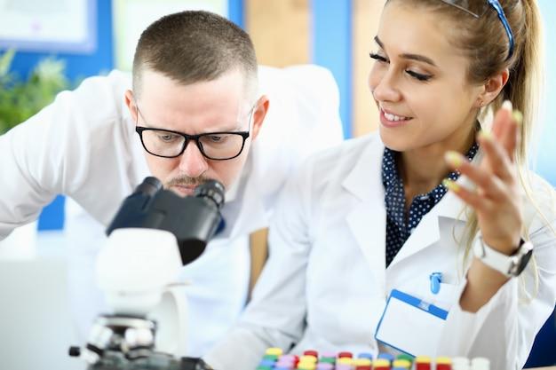 L'uomo e una donna guardano attraverso un microscopio in un laboratorio chimico Foto Premium