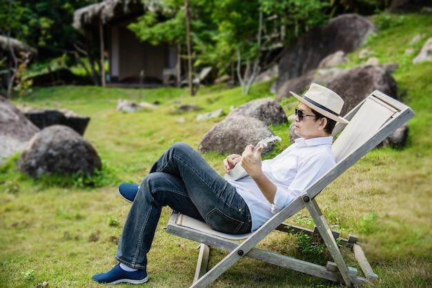 L'uomo felice gioca la chitarra nel giardino verde della natura Foto Gratuite