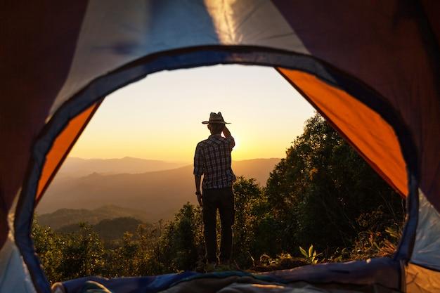 L'uomo felice resta vicino alla tenda intorno alle montagne sotto il cielo di luce del tramonto godendo il tempo libero e la libertà. Foto Gratuite