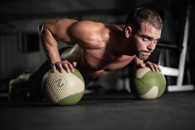 L'uomo fitness fa flessioni sulle palle Foto Premium