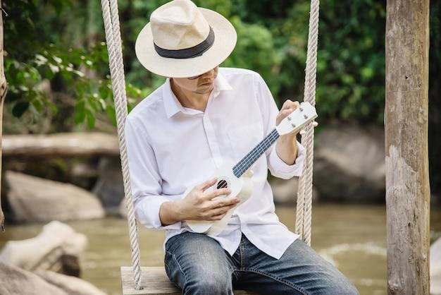 L'uomo gioca l'ukulele nuovo al fiume Foto Gratuite