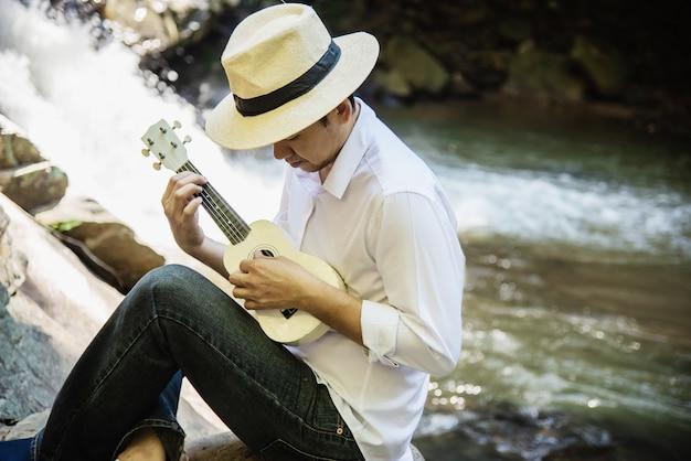L'uomo gioca l'ukulele nuovo alla cascata Foto Gratuite