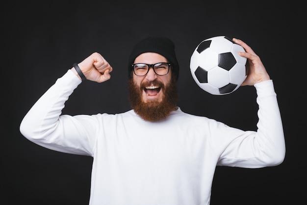 L'uomo giovane e barbuto sta tenendo un pallone da calcio e sta celebrando vicino alla parete nera. Foto Premium