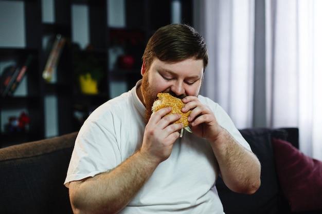 L'uomo grasso sorridente mangia l'hamburger che si siede prima di un set televisivo Foto Gratuite