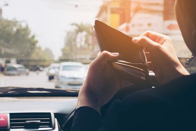 L'uomo guarda il suo portafoglio vuoto mentre guida la macchina, comportamento pericoloso Foto Gratuite