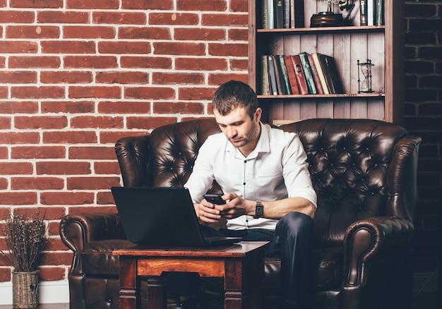 L'uomo impegnato chiama un numero di telefono. l'uomo d'affari è nel suo armadietto dietro il suo computer portatile Foto Premium