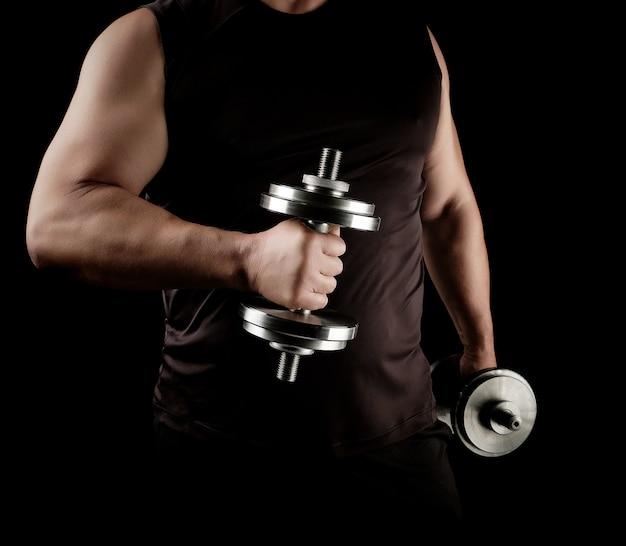 L'uomo in abiti neri tiene in mano manubri d'acciaio, i suoi muscoli sono tesi Foto Premium