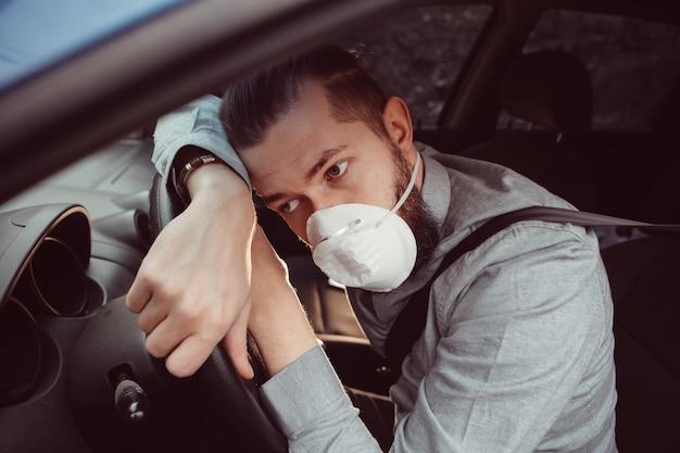 L'uomo in camicia e mascherina medica si siede al volante della macchina. Foto Premium