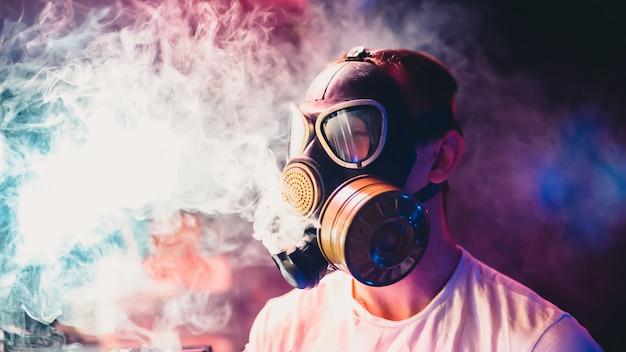 L'uomo in maschera antigas fuma un narghilè e respira una nuvola di fumo di tabacco Foto Premium