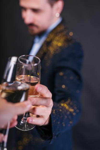 L'uomo in polvere scintillante che tintinnava il bicchiere di champagne Foto Gratuite