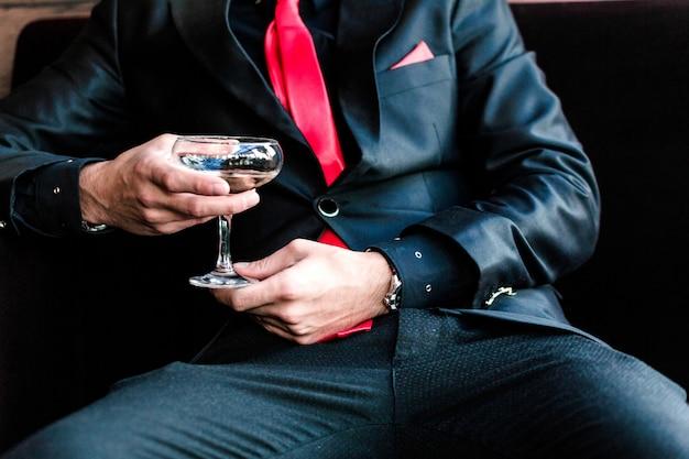 L'uomo in un vestito si siede e beve un cocktail Foto Premium