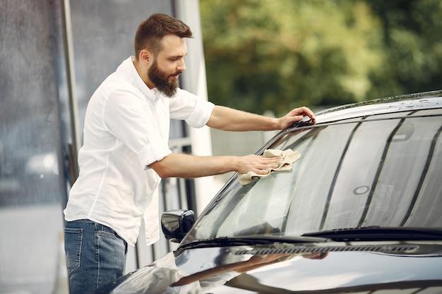 L'uomo in una camicia bianca pulisce un'auto in un autolavaggio Foto Gratuite