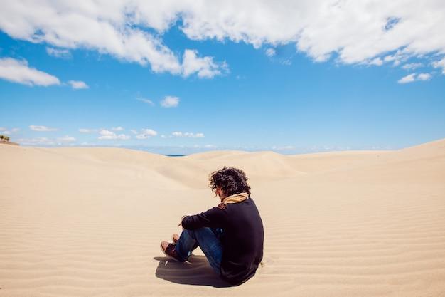 L'uomo irriconoscibile si siede su una duna del deserto. uomo che fa un giro turistico tra le dune in una calda giornata estiva. Foto Premium