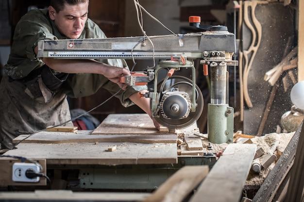 L'uomo lavora sulla macchina con il prodotto in legno Foto Gratuite