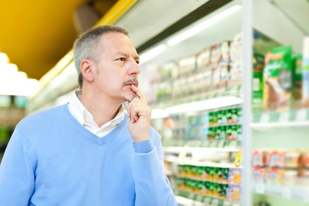 L'uomo lo shopping in un supermercato Foto Premium