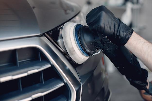 L'uomo lucidare un'auto in un garage Foto Gratuite