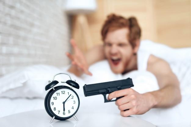 L'uomo malvagio svegliato punta la pistola alla sveglia, sdraiato sul letto Foto Premium