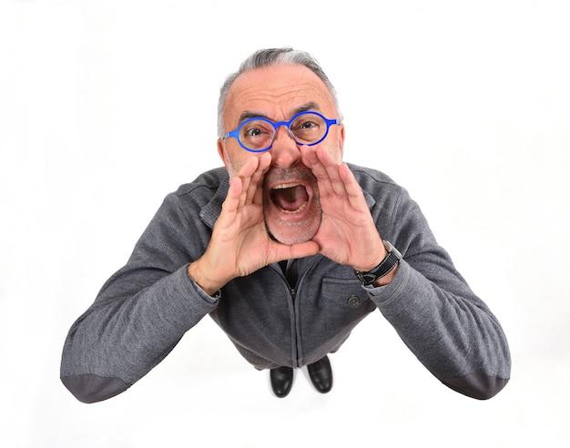 L'uomo mette una mano in bocca e sta urlando su bianco Foto Premium