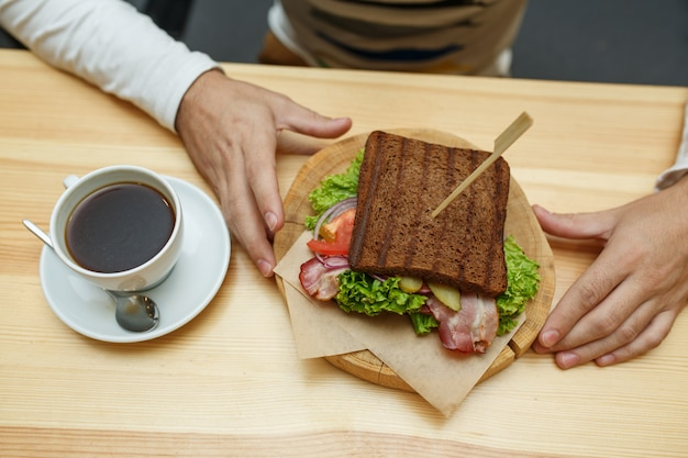 L'uomo nella caffetteria prende il suo panino e il caffè Foto Premium