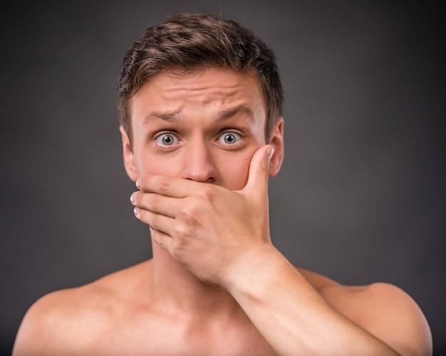 L'uomo nudo si alza e si copre la bocca con la mano. Foto Premium
