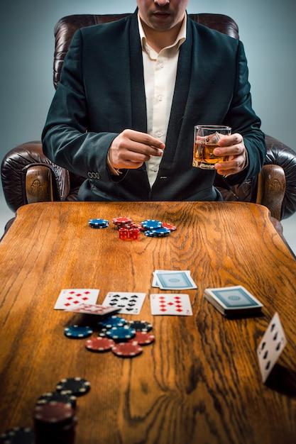 L'uomo, patatine per i giochi d'azzardo, bere e giocare a carte Foto Gratuite