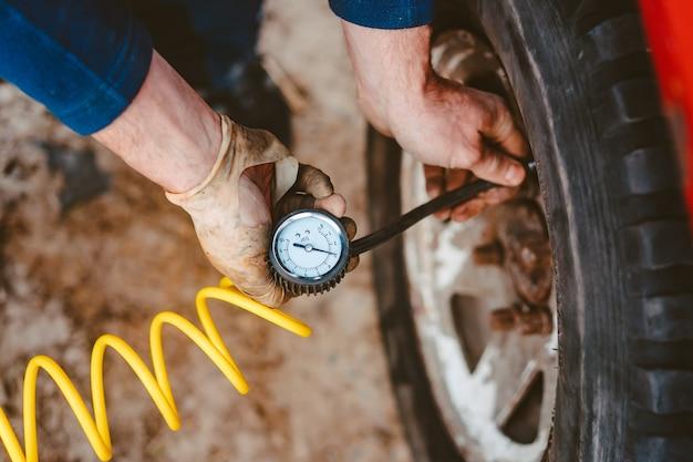 L'uomo pompa la ruota pneumatica con un compressore Foto Gratuite