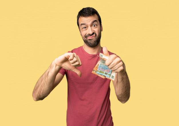 L'uomo prende un sacco di soldi facendo segno di buono-cattivo. indeciso tra sì o no su sfondo giallo isolato Foto Premium