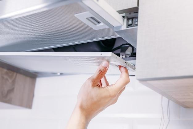 L'uomo ripara il cappuccio in cucina. filtro di ricambio in cappa Foto Premium