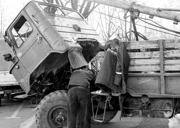 L'uomo ripara un camion sollevando una cabina Foto Premium