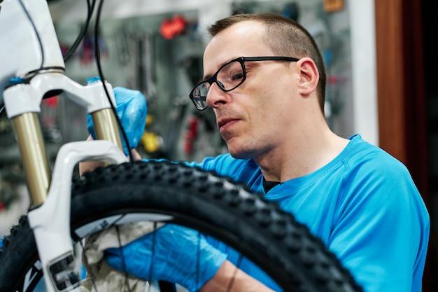 L'uomo ripara una bici nella sua piccola officina Foto Premium