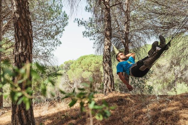 L'uomo riposo in amaca nella foresta Foto Gratuite