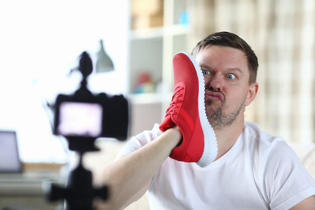 L'uomo scatta foto con la faccia di sneaker, fotocamera frontale Foto Premium