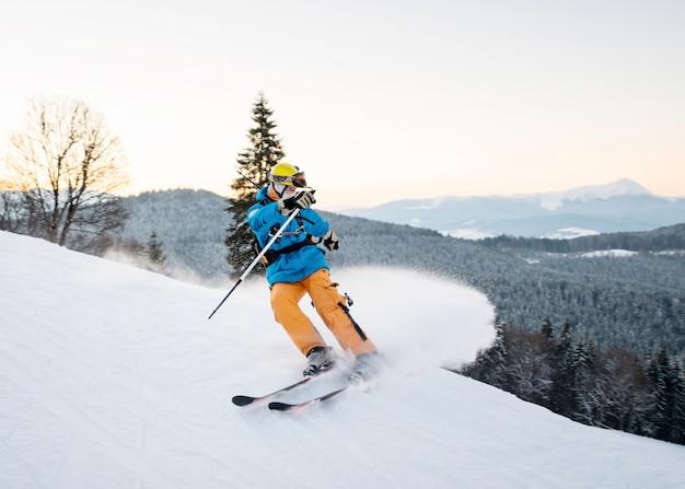 L'uomo sciatore in neve fresca produce frenate sul pendio della montagna Foto Premium
