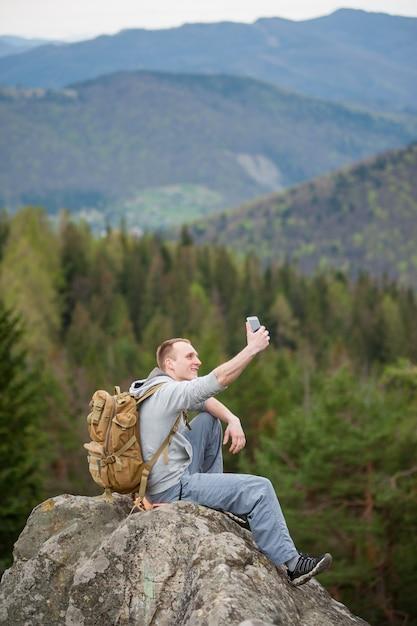 L'uomo seduto sul bordo di una roccia e fa selfie sul suo telefono Foto Premium