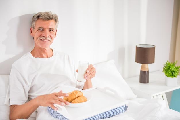 L'uomo senior felice sta facendo colazione a letto. Foto Premium