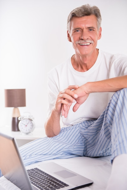 L'uomo senior sta usando il computer portatile mentre si sedeva a letto. Foto Premium