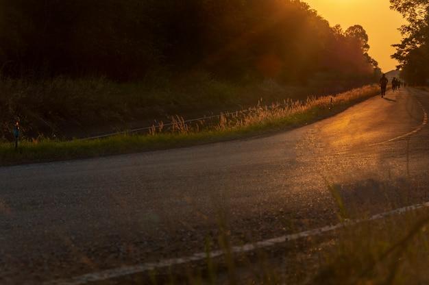 L'uomo sfocato sta facendo jogging sulla strada tra la luce del sole Foto Premium