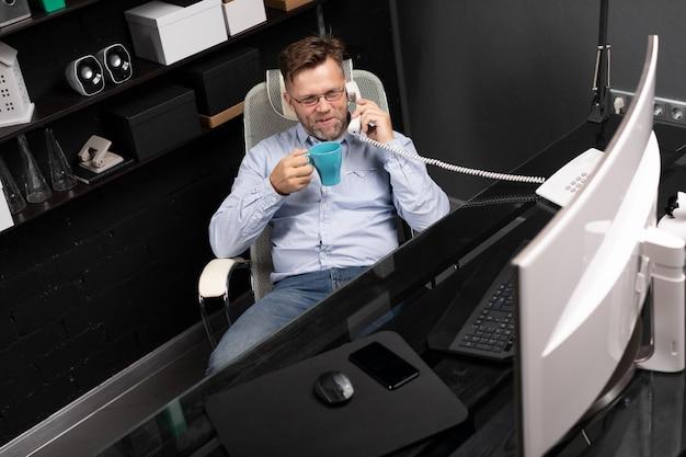 L'uomo si appoggiò allo schienale della sedia, bevendo caffè e parlando a telefono fisso Foto Premium